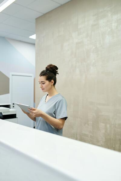 Woman standing at desk looking at tablet