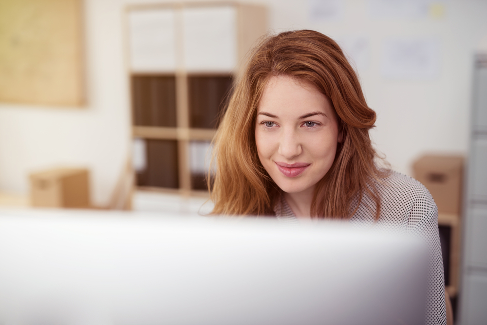 Smiling woman looking at computer monitor
